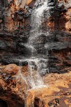 Beautiful View Of A Waterfall Flowing Between Fantastic Scultural Rocks  In Turkey.