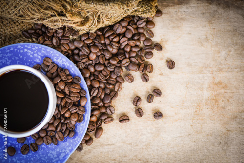 Door stickers Cafe Coffee cup on roasted coffee beans on sack and rustic wood background top view