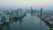 Aerial view of Bangkok skyline at dusk, Thailand. Skyscrapers by the river with boats