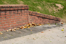 Sloped End Piece Of Old Brick Retaining Wall, Concrete With Magnolia Leaves, Horizontal Aspect
