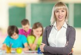Young female teacher with students in classroom - 264082642