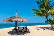 Couple beach chairs and coconut plam tree on tropical beach with sea and blue sky background. Summer background concept.