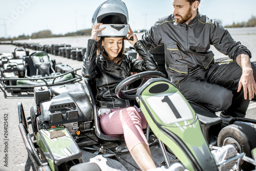 Fotografie, Obraz  Instructor with happy young woman driver wearing protective helmet before the ra