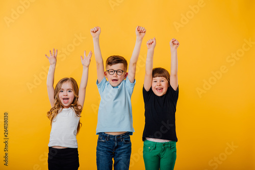 Fotografie, Obraz  three beautiful children, little boy in glasses and two little girls jumping up,