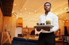 Young African American Waiter Man Hold Tray With Burger At Restaurant.