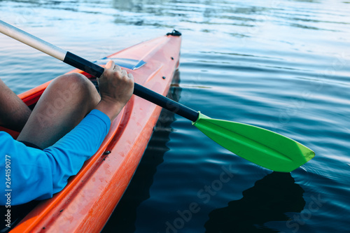 obraz lub plakat kayaker paddles across a serene lake, focus on the foreground
