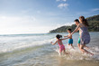 Happy young family running in sea water