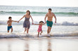 Happy young family running on beach
