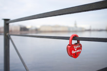 A Red Heart Shaped Padlock Hangs From A Railing With Two Russian Names Written On It. In Background Across River Is St Petersburg,Russia
