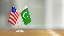 American And Pakistani Flag Pair On A Desk Over Defocused Background