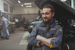 Cheerful bearded mechanic in grey uniform smiling to the camera, holding a wrench. Friendly car repairman resting at thegarage after examining broken car, copy space
