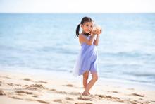 Happy Little Girl Listening To Seashell On Beach