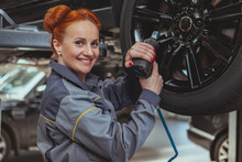 Beautiful Red Haired Female Mechanic Smiling To The Camera Over Her Shoulder, Holding Electric Wrench, Copy Space. Charming Woman Technician Servicing A Car At Her Workshop, Torquing Lug Nuts Of A Car