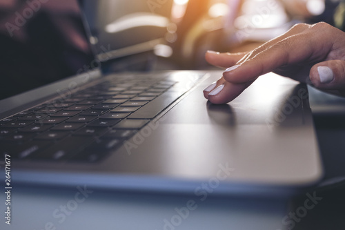 Fototapety, obrazy: Closeup image of a woman using and touching at laptop computer touchpad while sitting in the cabin