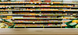 Supermarket, grocery department. Defocused, blurred image. In the foreground is the top of a wooden table, counter.
