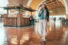 Full Length Young Asian Girl Tourist Walking Indoor Sightseeing Looking Enjoy Restored Art Deco Interior Of Union Station While Travel By Train In America. Background Passengers Ask Information Desk