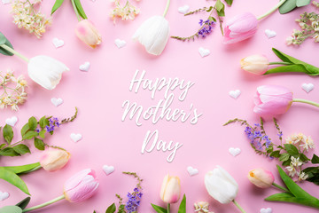 Happy mothers day concept. Top view of pink tulip flowers in frame with happy mother's day text on pink pastel background. Flat lay.