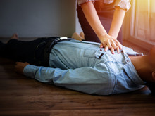 Volunteer Office Woman Use Hand Pump On Chest For First Aid Emergency CPR On Heart Attack Man Unconscious, Try To Resuscitation Patient Man At Work
