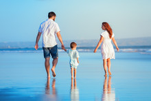 Happy Family - Young Father, Mother, Baby Son Strolling Together, Child Run With Fun By Water Pool Along Sunset Sea Surf On Tropical Beach. Travel Lifestyle, People Walking With Kid On Summer Vacation