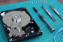 The Disassembled Hard Disk On The Desk A Green Substrate