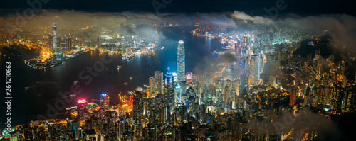 Valokuva  Panorama aerial view of Hong Kong City skyline at night over the clouds