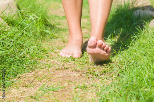Fotografie, Obraz Young woman barefoot walking on natural trail in sunny summer day