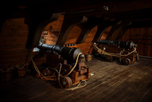 Interior View Of Cannons At The Deck And Cannon Balls Plus Windows On Old Galleon With Ropes.