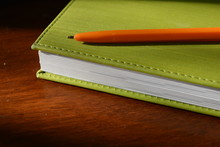 A Green Cover Book With A Bright Orange Pen On A Wooden Lacquer Table, Business Background