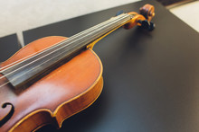 The Violin On The Dark Table, Close - Up Of Violin On The Wooden Floor, Top View Of Violin Musical On Dark Wooden Floor, Vintage And Classic Musical Instrument Used In The Orchestra.