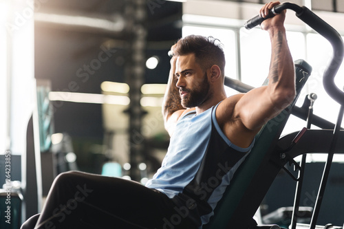 Young man exercising with training apparatus in gym, empty space Wallpaper Mural