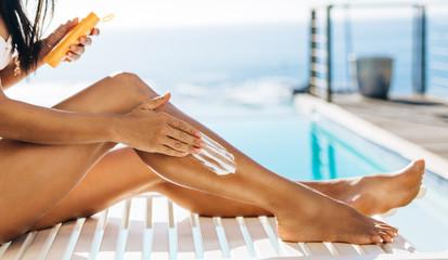 Woman putting tanning cream on legs