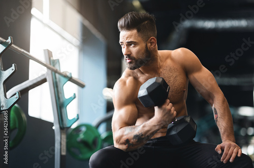 Spoed Foto op Canvas Ontspanning Strong muscular man doing exercises with dumbbells