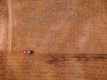 Agriculture Tractor Plows Field Of Land For Sowing. Top View Aerial Photo.