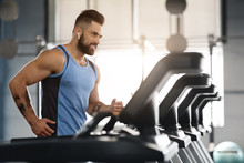 Young Handsome Man Running On Treadmill At Gym
