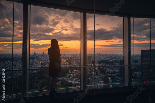 Canvas Print Rear view of Traveler woman looking Tokyo Skyline and view of skyscrapers on the observation deck at sunset in Japan