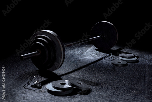 Fényképezés  365 pound weight on barbell with weights on floor and collars in dramatic lighti