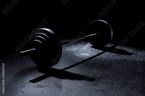 Fototapeta  365 pound weights in gym on barbell with dramatic lighting