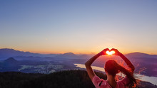 Girl Forming A Heart With Her Hands, Holding Sun In The Hands' Frame. Below Is Wörthersee, Austria.  Soft Colors Of The Sunrise. Share Love Not Hate. Long Hair Blown By The Wind. Pyramidenkogel