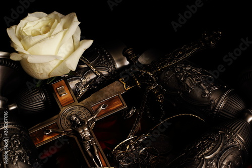 Fotografie, Tablou Stiletto, crucifix with inlaid metal chain, metal goblets for wine and white rose on black background