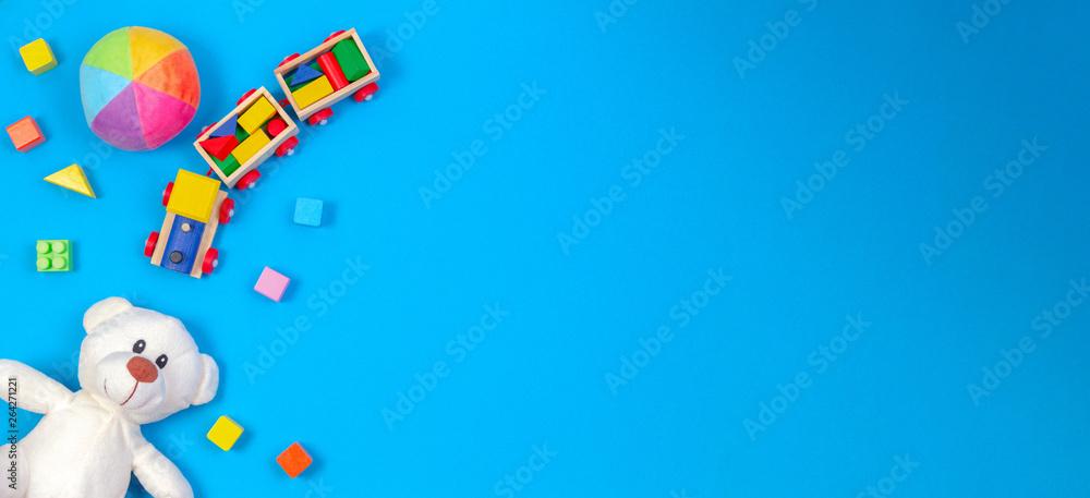 Fototapety, obrazy: Baby kids toys background. White teddy bear, wooden train, colorful blocks on blue background