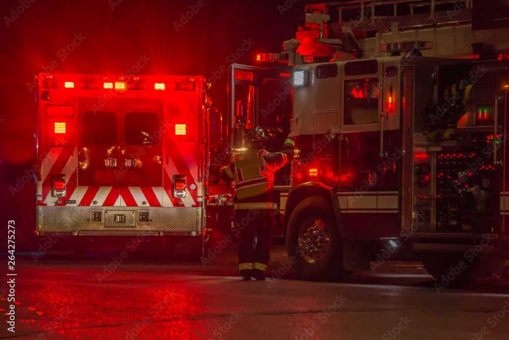 Fototapeta fire truck, firefighter, ambulance responding to car crash at night
