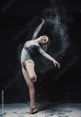 Küchenrückwand aus Glas mit Foto Tanzschule A young beautiful girl in a swimsuit and a translucent skirt emotionally dancing on a black background in clouds of white dust