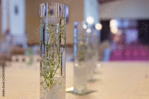 Foto auf AluDibond Maiglöckchen lily of the valley in water in transparent vase. restaurant hall