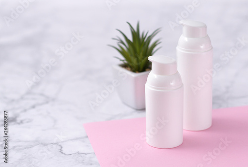 Poster Spa Cosmetic bottle with green plant on marbel background. Natural beauty product concept.