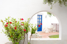 Red Hibiscus And Traditional Greek House With Blue Door