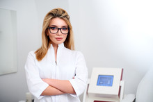 Smiling Confident Female Doctor With Lab Coat On Standing In Her Office With Medical Hardware And Patient Chair On Background. Practician Woman Wearing White Hospital Uniform And Stylish Glasses.