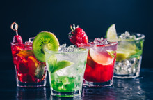 Four Colorful Tasty Alcoholic Cocktails In A Row At The Bar Stand. Luxury Vacation Concept. Toned Image