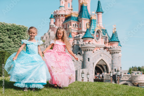 Little adorable girls in beautiful princess dress at fairy-tale park Fototapet