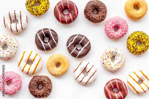 Traditional american donuts of different flavors on white background flat lay pattern