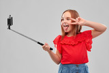 childhood and people concept - beautiful smiling girl in red shirt and skirt taking picture by smartphone on selfie stick and showing peace over grey background
